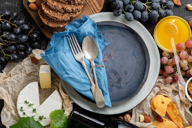 Leere blaue platte mit gabellöffel im rahmen von lebensmittelzutaten mediterrane küche. blauer teller teller im rahmen von essen wein käse brottrauben.