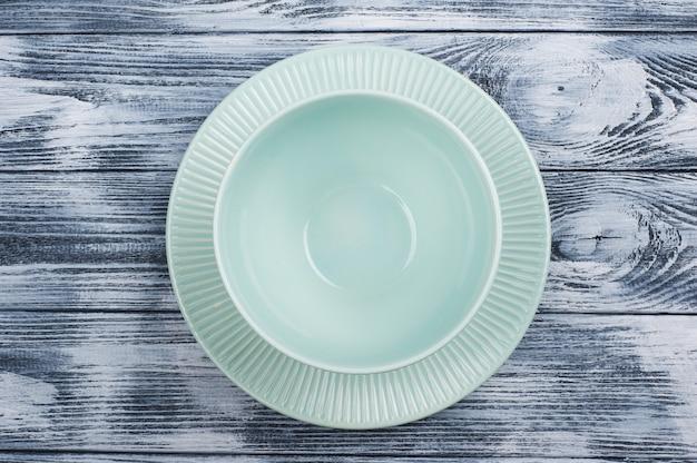 Leere blaue platten über holztisch