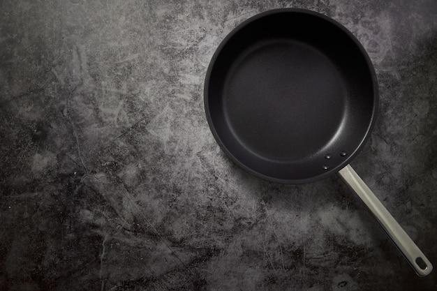 Leere bratpfanne schwarz auf dunklem stein arbeitsfläche mit exemplar