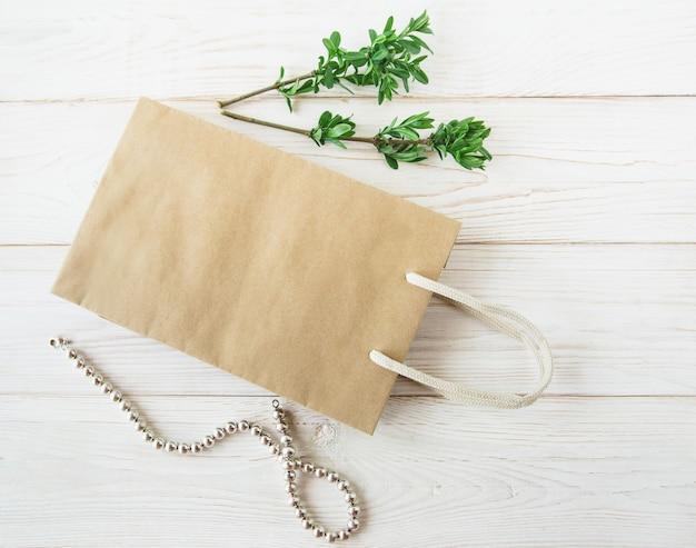 Leere braune bastelpapiertüte mit griffenfrischgrüne blätter und halsketteweißer hintergrund