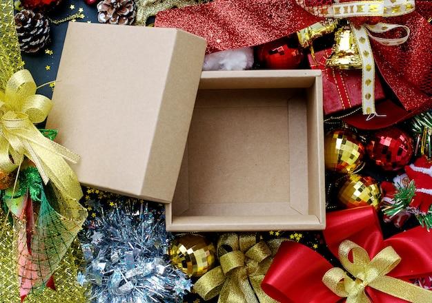 Leere braune beige geschenkbox mit rotem und goldenem weihnachtsschmuck