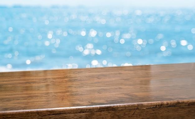 Leere braune glatte hölzerne tischplatte mit unschärfehimmel und meer boekh hintergrund