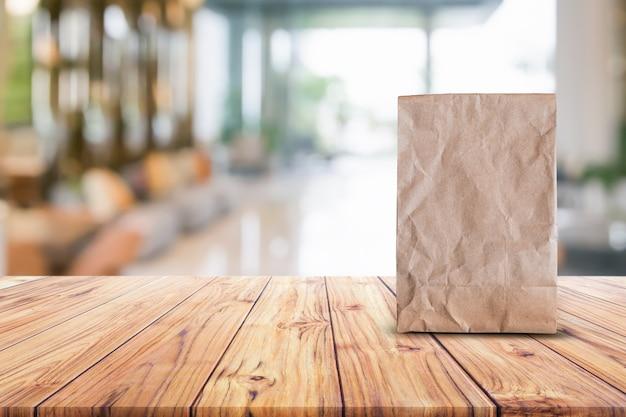 Leere braune papiertüte für das mitnehmen von lebensmitteln auf hölzerner tabelle verwischte abstrakte hintergrundinnenansicht f
