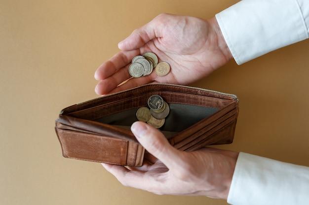 Leere brieftasche in den händen des mannes draufsicht münzen in der hand und in einer leeren brieftasche. konkurs und insolvenz in wirtschaft und finanzen