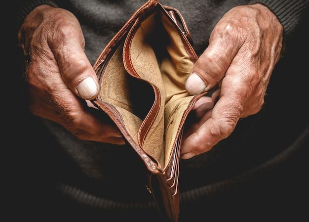 Leere brieftasche in den händen eines älteren mannes