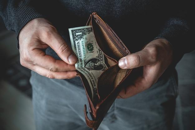 Leere brieftasche in den händen eines jungen mannes