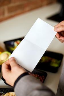 Leere broschüre in händen auf dem hintergrund des essens in kisten