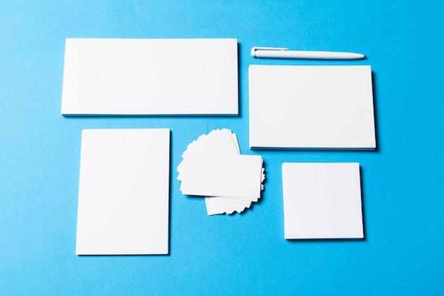 Leere bürogegenstände organisiert für firmendarstellung auf blauem papier