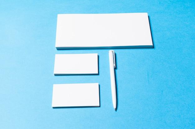 Leere bürogegenstände organisiert für firmendarstellung auf hintergrund des blauen papiers