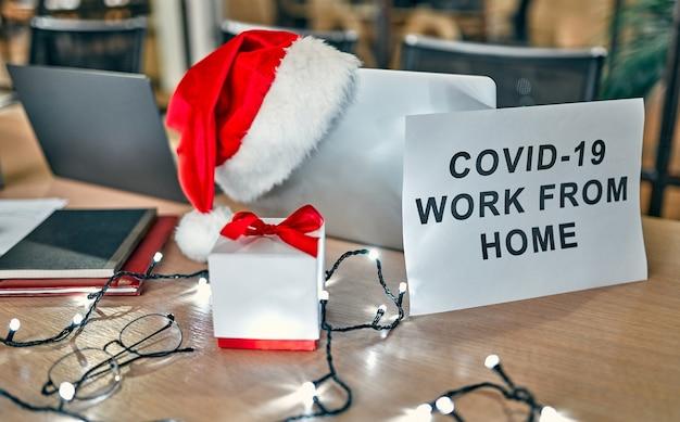 Leere büroräume mit weihnachtsmütze und geschenkbox, während der beamte von zu hause aus arbeitet, um coronaviren zu vermeiden.