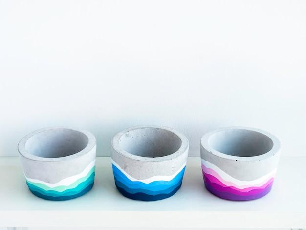 Leere bunte diy runde betontöpfe auf einem weißen holzregal auf weißer wand mit kopienraum. drei einzigartige bunt bemalte zementpflanzgefäße.