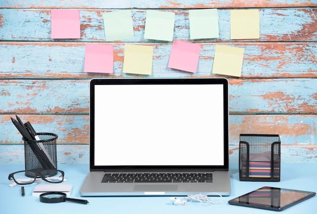 Leere bunte klebende anmerkungen gegen hölzerne wand mit büromaterialien und laptop