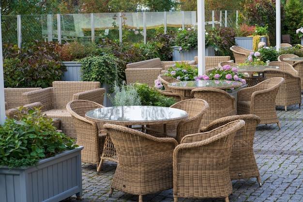 Leere caféterrasse im freien mit korbmöbeln und wachsenden blumen im topf für die sommerunterhaltung