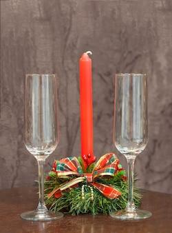Leere champagnergläser auf einem hintergrund von roten kerzen in einem weihnachtskerzenhalter
