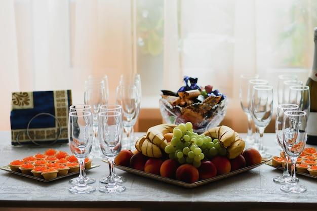 Leere champagnergläser und -frucht auf dem tisch