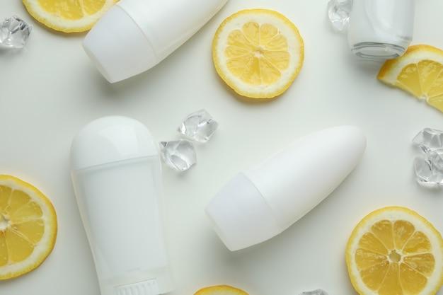 Leere deodorants, zitronenscheiben und eiswürfel auf weißem hintergrund
