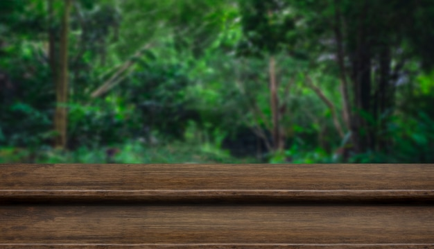 Leere dunkle holz-tischplatte des stufengrunge mit unschärfebaum im tropischen wald mit bokeh