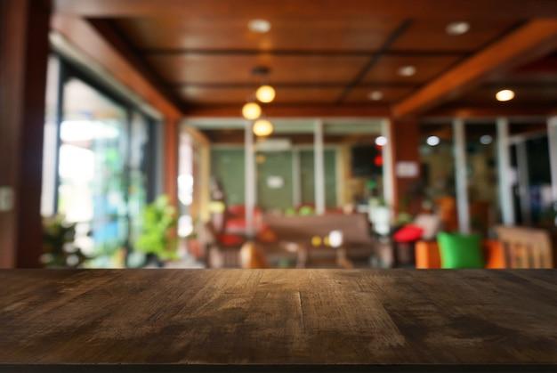 Leere dunkle holztisch vor abstrakten unscharfen hintergrund des cafés und cafés innenraum. kann für die anzeige oder montage ihrer produkte verwendet werden.