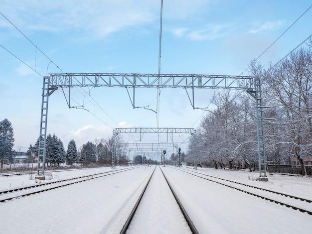 Leere eisenbahnschienen unter den weißen winterschneeverwehungen, landbahn.