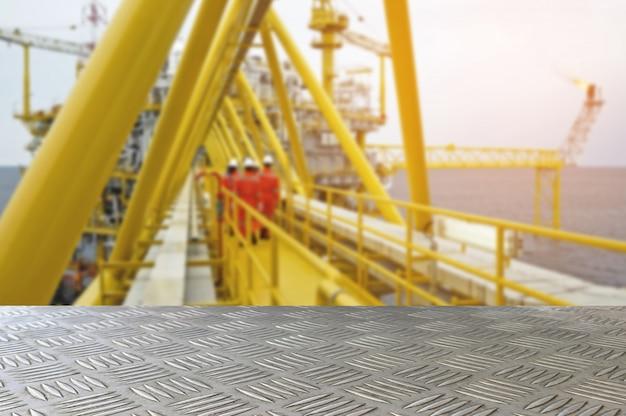 Leere eisenplattentabelle mit öl- und gasplattform- oder bauplattformoffshoreplattform-unschärfehintergrund für darstellung und advertorial.