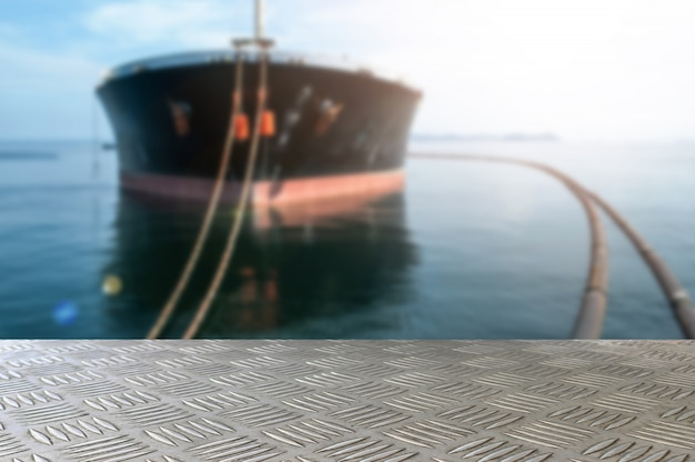 Leere eisenplattentabelle mit öltankerrohr-übergabestation im seeunschärfehintergrund für darstellung und advertorial.