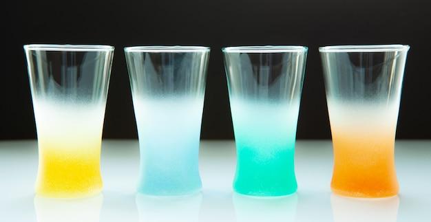 Leere farbige gläser für verschiedene getränke auf einem dunklen hintergrund
