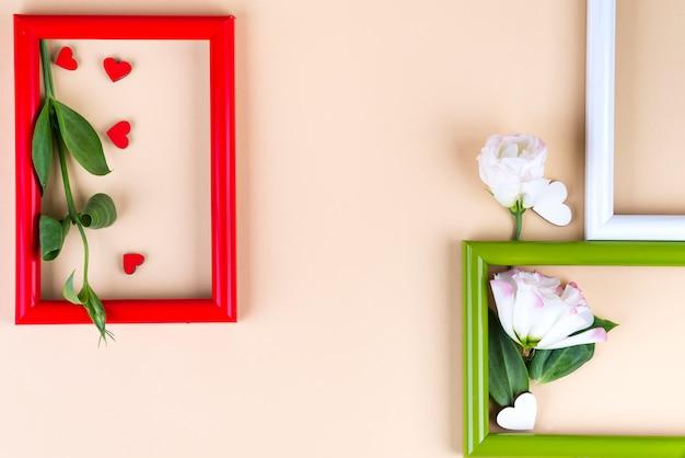 Leere farbrahmen, rote herzen und blumen eustoma auf beige oberfläche mit kopienraum.