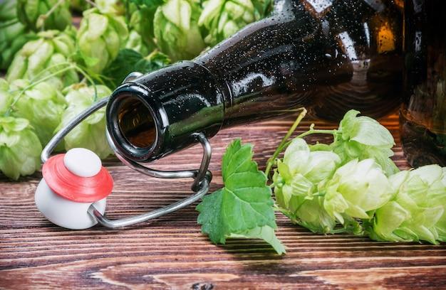 Leere flasche bier und hopfenpflanze