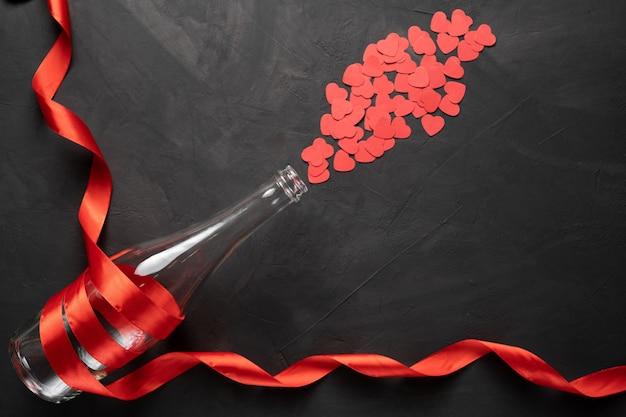Leere flasche champagner in einem roten band herzen in form von spritzern. valentinstag. auf einem konkreten hintergrund. freier speicherplatz für ihren text.