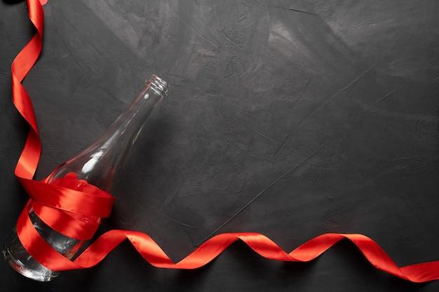 Leere flasche champagner in einem roten band. valentinstag. auf einem konkreten hintergrund. freier speicherplatz für ihren text.