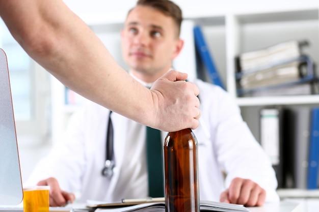 Leere flasche des alkoholikers in der hand an der rezeption des arztes