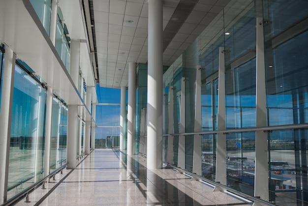 Leere flughafenhalle mit glasfenstern und weißer säule.
