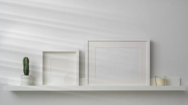 Leere fotorahmen und dekorationen auf weißem regal mit weißer wand