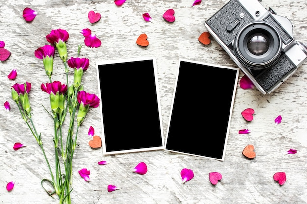 Leere fotorahmen, vintage retro-kamera und lila nelkenblumen