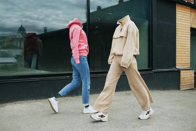 Leere frauenkleider gehen auf der straße mit kapuze, jeanshose, turnschuhen und bunten turnschuhen.