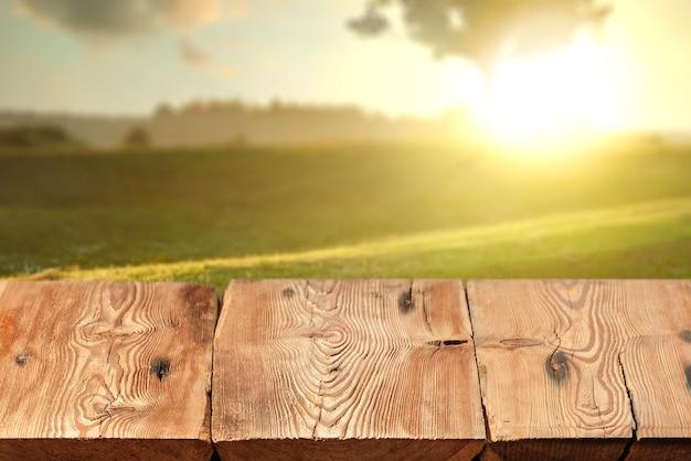 Leere gealterte strukturierte harte hölzerne tabelle auf einem unscharfen natürlichen ländlichen sonnenuntergangshintergrund der natur für das aussetzen und montieren ihrer produkte.