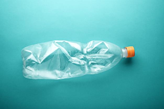 Leere gebrauchte plastikflasche auf neo-minze-hintergrund. konzept der umweltverschmutzung
