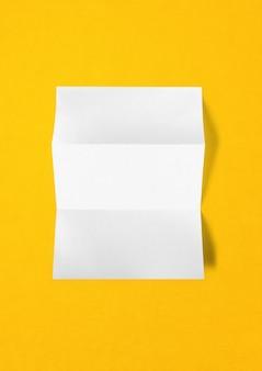 Leere gefaltete weiße a4-papierblatt-modellschablone lokalisiert auf gelbem hintergrund