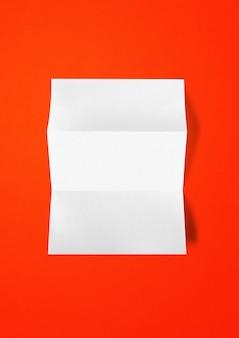 Leere gefaltete weiße a4-papierblatt-modellschablone lokalisiert auf rotem hintergrund