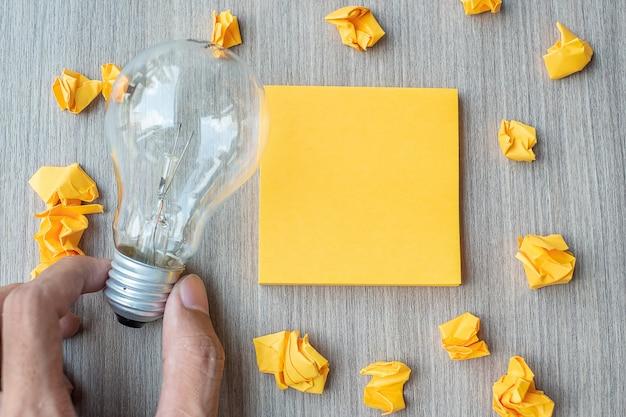 Leere gelbe anmerkung und zerfallenes papier mit dem geschäftsmann, der glühlampe hält
