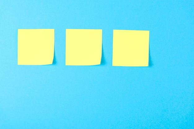 Leere gelbe haftnotizen auf blau