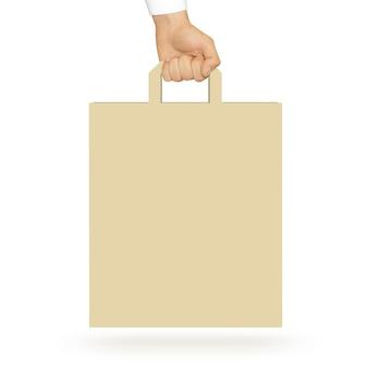 Leere gelbe papiertüte, die in der hand hält