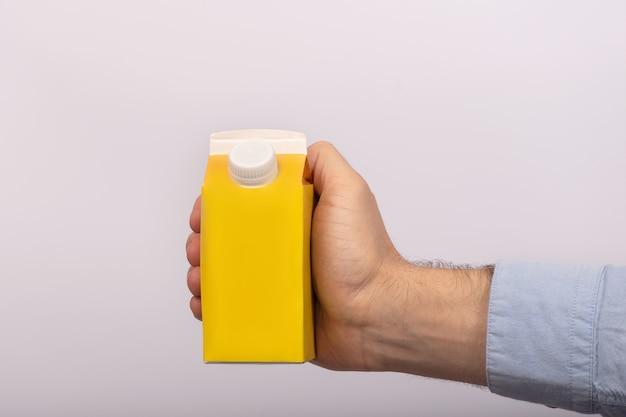 Leere gelbe papptasche mit kappe in der hand des mannes. päckchen saft oder milch. attrappe, lehrmodell, simulation.