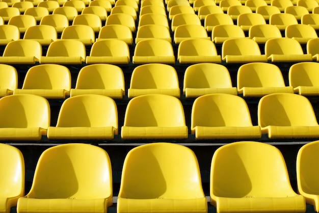 Leere gelbe plastiksitze im stadion, sportarena mit offener tür.