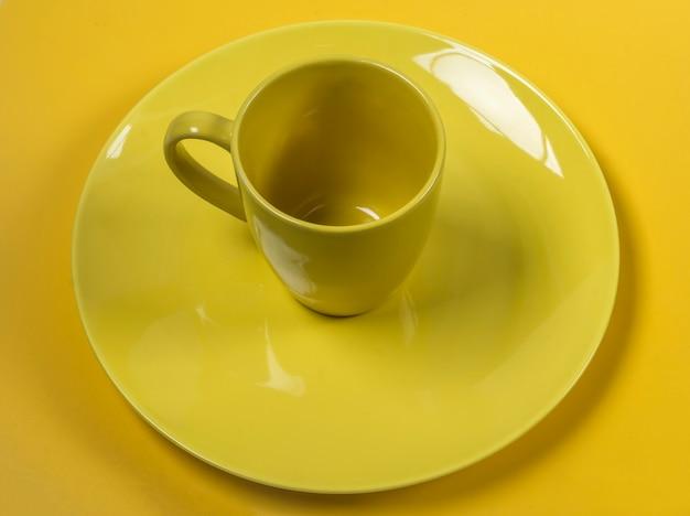 Leere gelbe platte und tasse auf gelber hintergrundoberansicht.