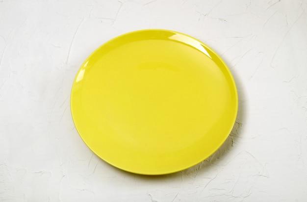 Leere gelbe schale auf weißem strukturiertem hintergrund.