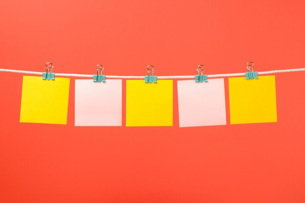 Leere gelbe und rosa papieranmerkungen über die schnur