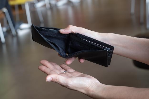 Leere geldbörse in den händen der frau.