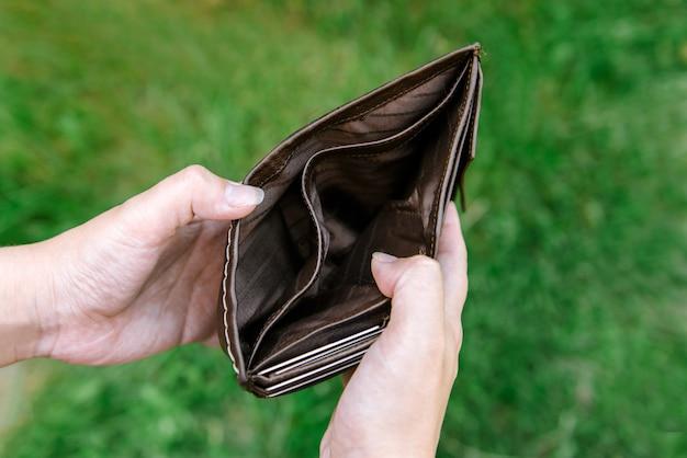 Leere geldbörse in den händen der frau