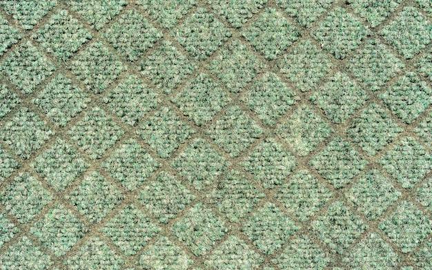 Leere generische nahtlose grüne teppich textur hintergrund, muster im freien, kunststoff stoff textur nahaufnahme. graues kontrastdiamantmuster
